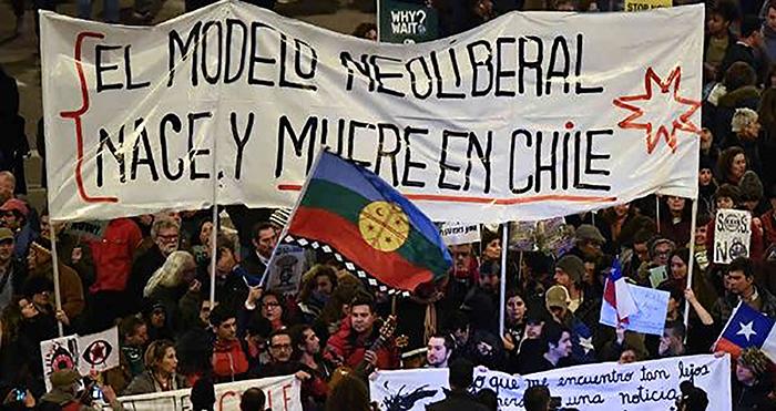 Fotografía de movilización con cartel El modelo Neoliberal Nace y Muere en Chile